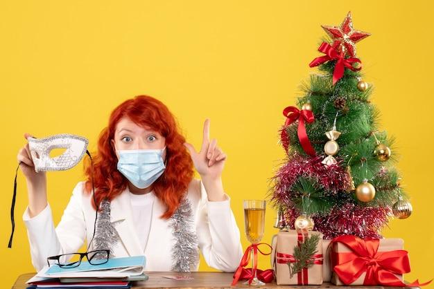 Vue de face femme médecin en masque stérile tenant un masque de fête