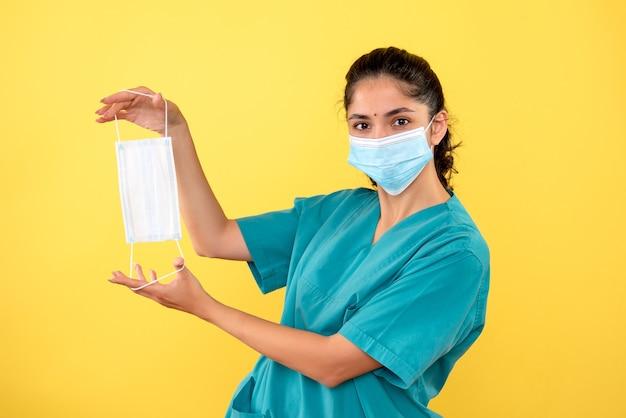 Vue de face de femme médecin avec masque tenant un masque dans ses mains sur un mur jaune