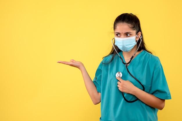 Vue de face femme médecin avec masque tenant le stéthoscope dans sa main pointant vers la gauche