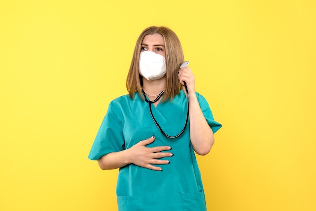 Vue de face de la femme médecin avec masque et tonomètre sur mur jaune