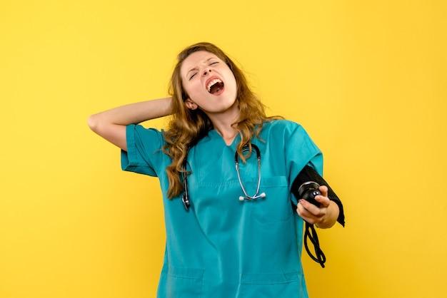 Vue de face femme médecin mesurant la pression sur l'espace jaune