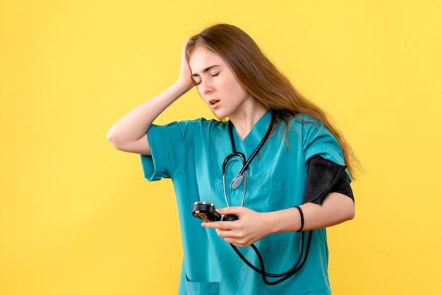 Vue de face femme médecin mesurant la pression sur fond jaune hôpital médical médical