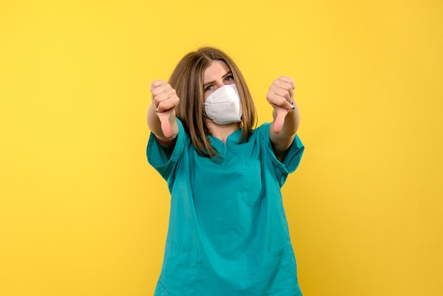 Vue de face femme médecin montrant signe différent sur l'espace jaune