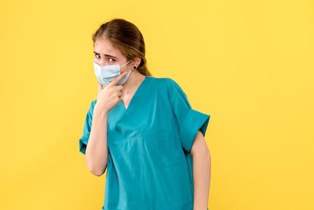Vue de face femme médecin pensant au masque sur fond jaune pandémie de covid hôpital