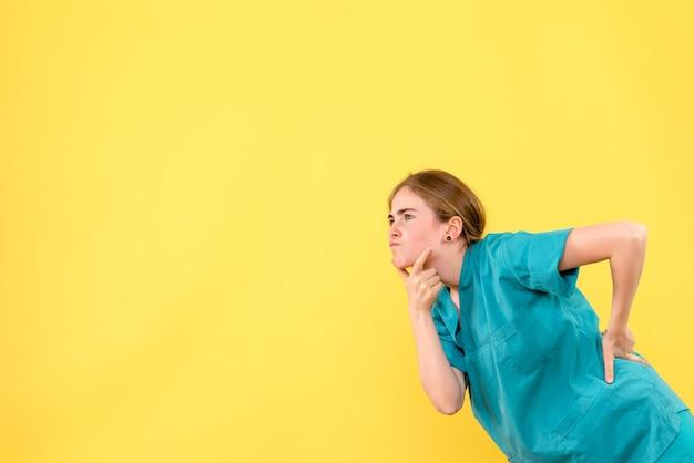 Vue de face femme médecin pensant sur fond jaune médical émotions virus virus de la santé de l'hôpital