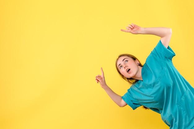 Vue de face femme médecin pointant sur fond jaune médical émotion virus santé hospitalière