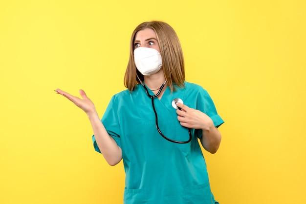 Vue de face femme médecin portant un masque stérile sur l'espace jaune
