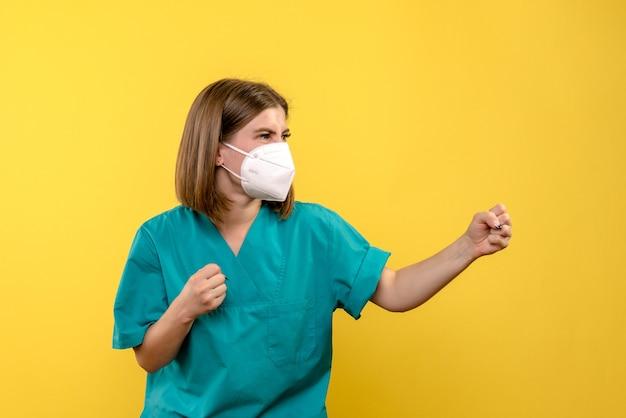 Vue de face femme médecin posant avec colère sur l'espace jaune