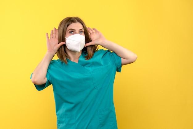 Vue de face femme médecin posant sur l'espace jaune