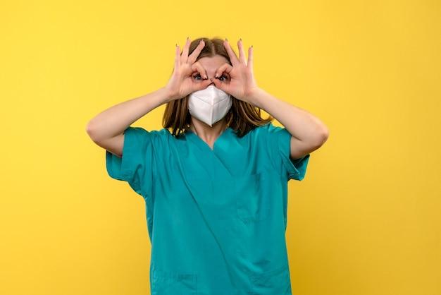 Vue de face femme médecin posant avec masque sur espace jaune