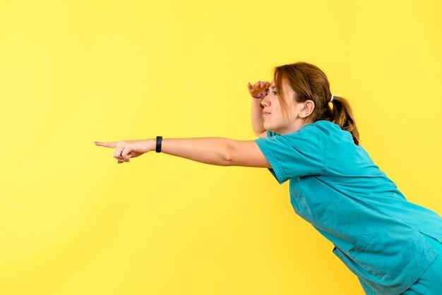 Vue de face femme médecin regardant à distance sur l'espace jaune