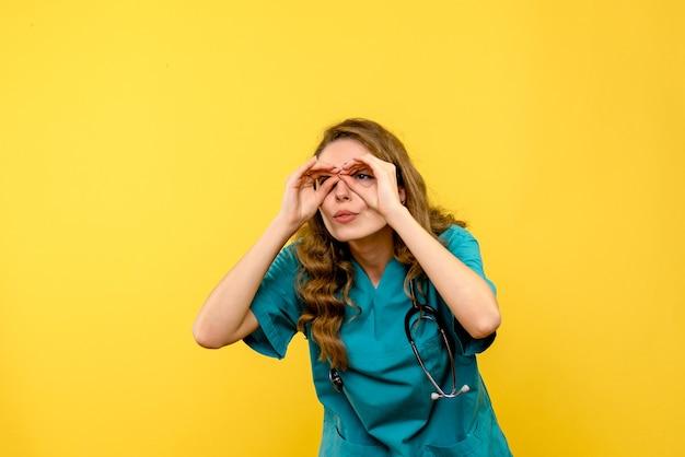 Vue de face femme médecin regardant à travers les doigts sur l'espace jaune