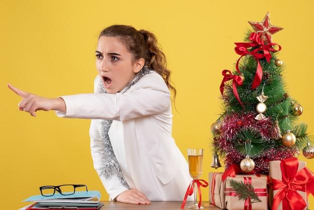 Vue de face femme médecin se disputant autour des cadeaux de noël et de l'arbre