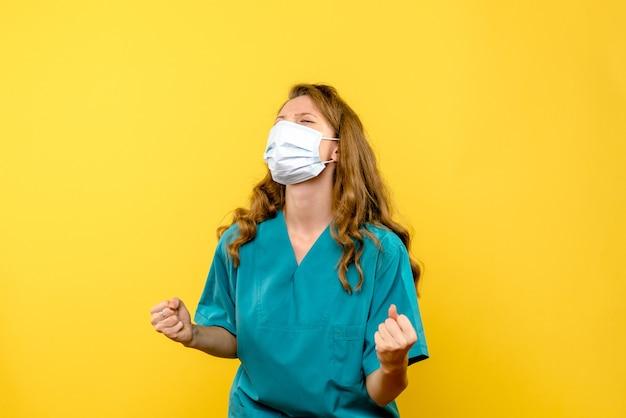 Vue de face femme médecin se réjouissant de masque sur l'espace jaune