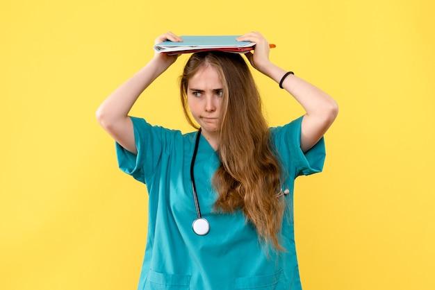 Vue de face femme médecin a souligné avec des analyses sur la santé de l'hôpital médical fond jaune