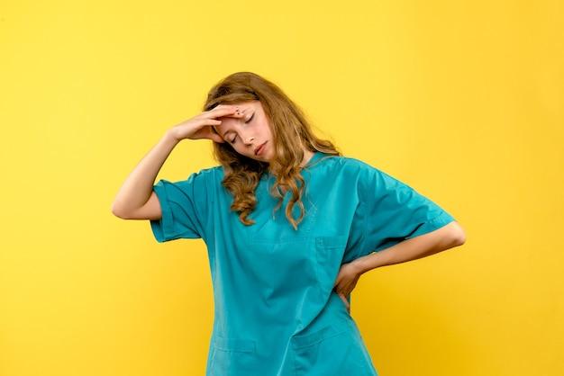 Vue de face de la femme médecin a souligné sur le mur jaune