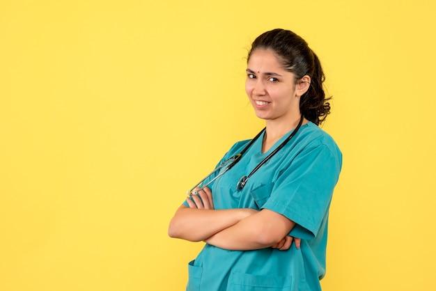 Vue de face femme médecin avec stéthoscope croisant ses mains debout