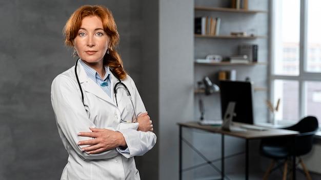 Vue de face de la femme médecin avec stéthoscope posant au bureau