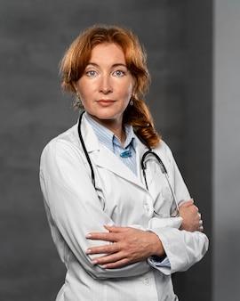 Vue de face de la femme médecin avec stéthoscope posant les bras croisés