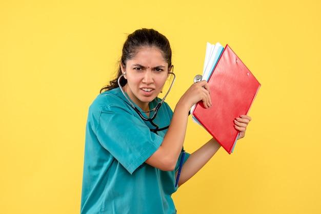 Vue de face femme médecin avec stéthoscope tenant des dossiers debout