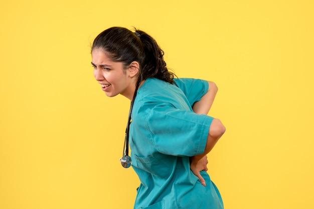 Vue de face femme médecin avec stéthoscope tenant son dos debout