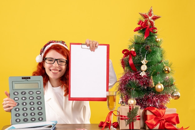 Vue de face femme médecin tenant calculatrice autour des cadeaux de noël et arbre