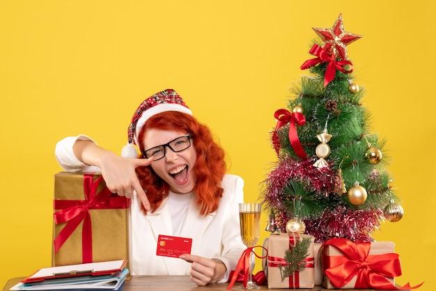 Vue de face femme médecin tenant une carte bancaire autour de cadeaux de noël et arbre