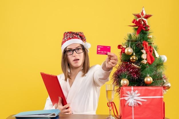 Vue de face femme médecin tenant une carte bancaire et une note de fichier