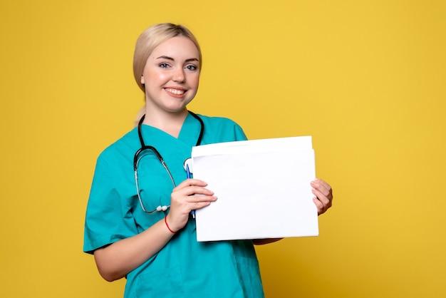 Vue de face femme médecin tenant différents papiers, virus de l'infirmière de l'hôpital de la santé pandémique covid-19