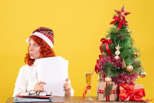 Vue de face femme médecin tenant des documents et assis avec des cadeaux de noël