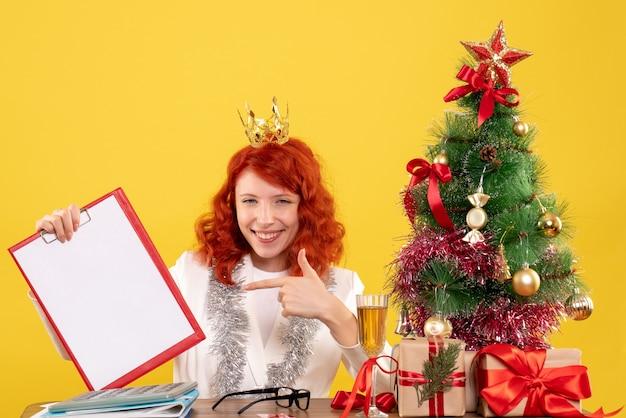 Vue de face femme médecin tenant la note de fichier autour des cadeaux de noël et de l'arbre