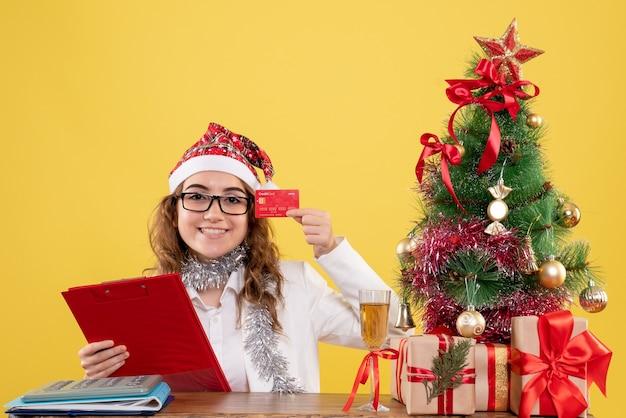 Vue de face femme médecin tenant note de fichier et carte bancaire