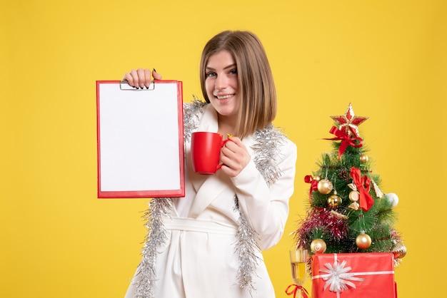 Vue de face femme médecin tenant note de fichier et tasse de thé