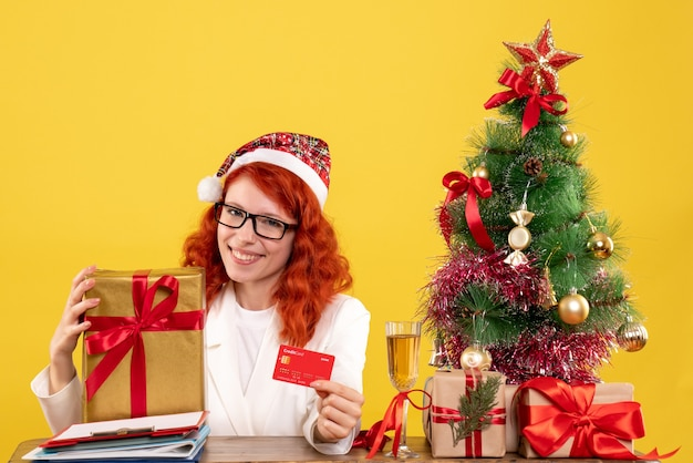 Vue de face femme médecin tenant présent et carte bancaire