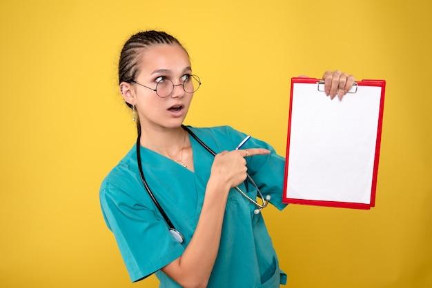Vue de face femme médecin tenant presse-papiers médical et stylo, couleur infirmière hôpital émotion covid-19 santé