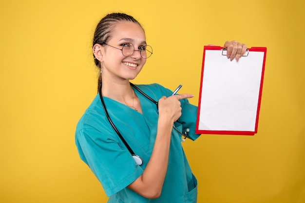 Vue de face femme médecin tenant presse-papiers médical et stylo avec sourire, couleur infirmière hôpital émotion covid-19 medic health