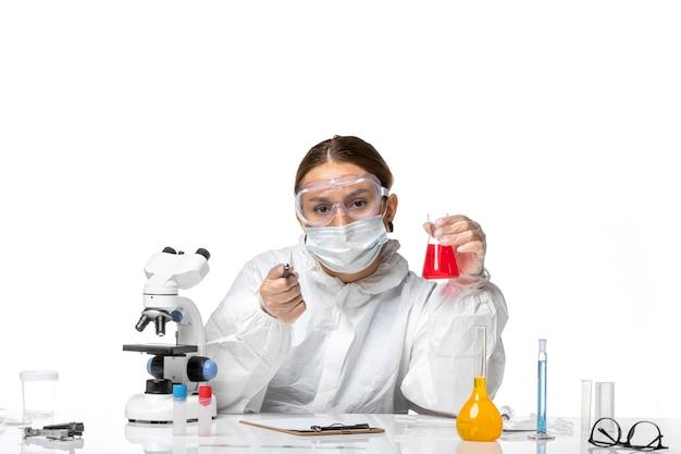 Vue de face femme médecin en tenue de protection et avec masque tenant flacon avec une solution rouge sur fond blanc coronavirus pandémique du virus covid