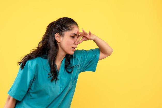 Vue de face femme médecin en uniforme fermant son nez
