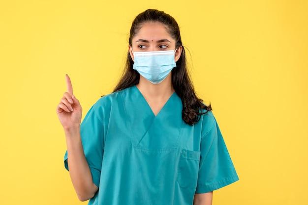 Vue de face femme médecin en uniforme levant la main debout