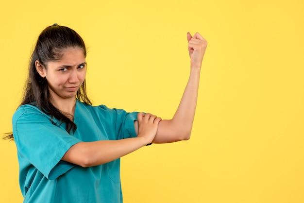 Vue de face femme médecin en uniforme montrant les muscles du bras debout