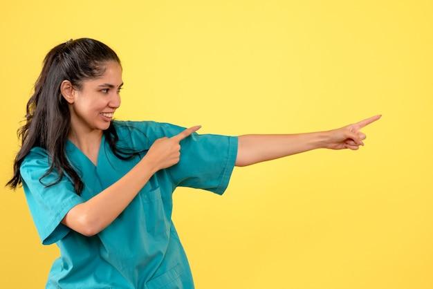 Vue de face de la femme médecin en uniforme pointant vers la bonne direction sur le mur jaune