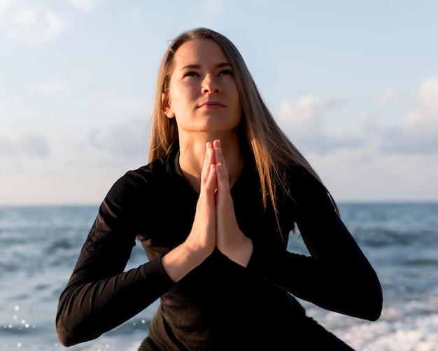 Vue de face femme méditant sur la plage