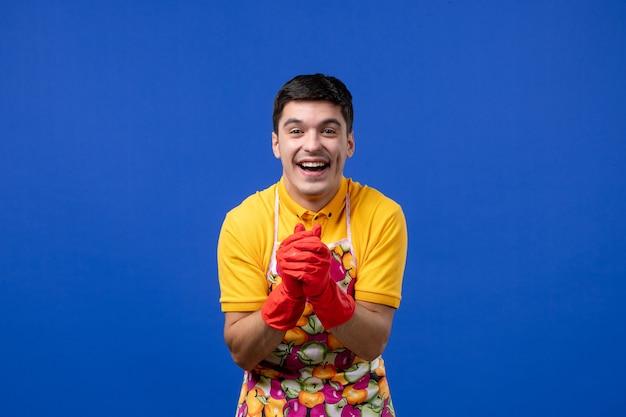 Vue de face femme de ménage homme riant en tablier joignant les mains