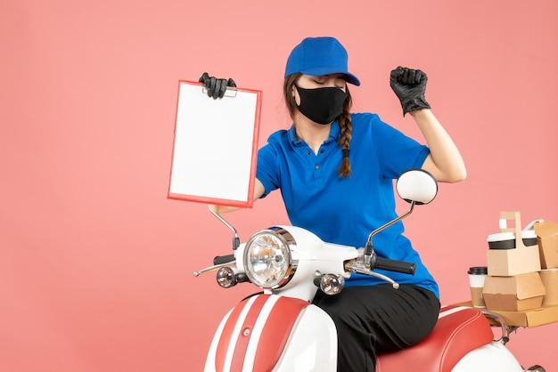 Vue de face d'une femme de messagerie émotionnelle heureuse portant un masque médical et des gants assis sur un scooter tenant des feuilles de papier vides livrant des commandes sur fond de pêche pastel