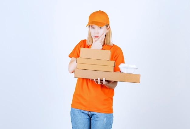 Vue de face de la femme de messagerie qui met sa main près de son menton et pense tout en tenant les boîtes et le bol en plastique
