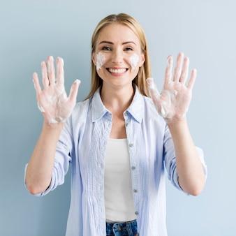 Vue de face de femme montrant ses mains savonneuses