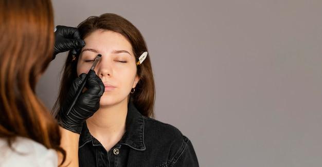 Vue de face de la femme obtenant un traitement des sourcils du clinicien avec copie espace