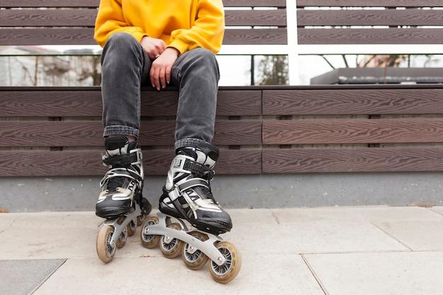 Vue de face de femme en patins à roues alignées assis sur un banc