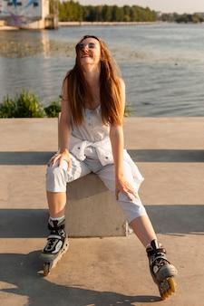 Vue de face de la femme avec des patins à roulettes posant au bord du lac