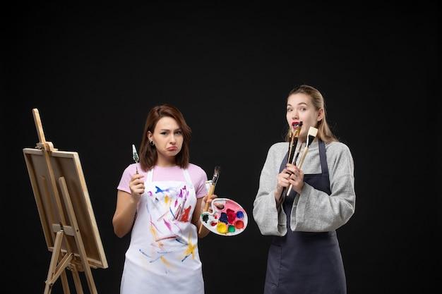 Vue de face femme peintre dessin sur chevalet avec d'autres femmes sur fond noir photo de l'artiste couleur art photos travail de peinture dessiner